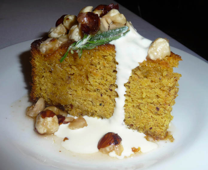 Hazelnut Mascarpone cake served with rosemary, fresh cream and raw hazelnuts