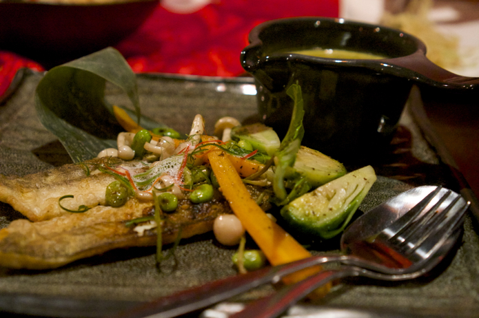 Deconstructed green curry. Pan fried fish, roasted vegetables and a green curry sauce.