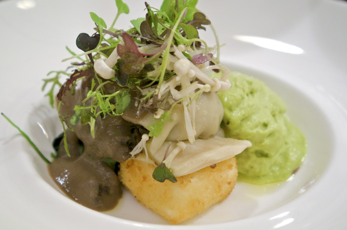 Mushroom raviolo served with an asparagus foam, a truffled sauce and micro herbs