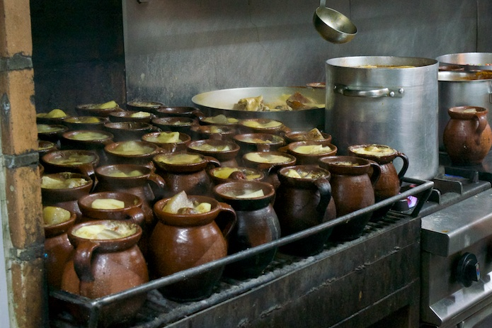La Bola's famous stew cooks in clay pots for hours over a charcoal fire